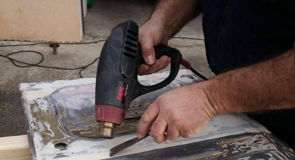 Décapeuse thermique sur une pièce de métal.