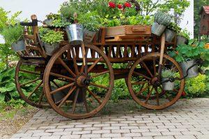 Charrette en bois vieillie soutenant des bacs de fleurs