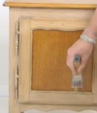 Application d'une couche de résine acrylique sur un meuble en bois