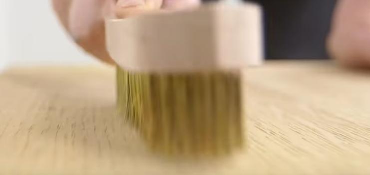 Application d'une brosse à cérer sur la surface d'un meuble en bois