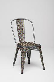 Chaise tolix modele a décorée avec des rivets et des disques de cuir