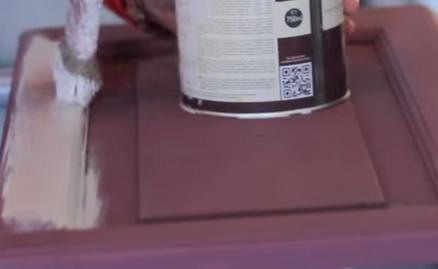 Application d'une couche de peinture blanche sur une porte de placard en bois