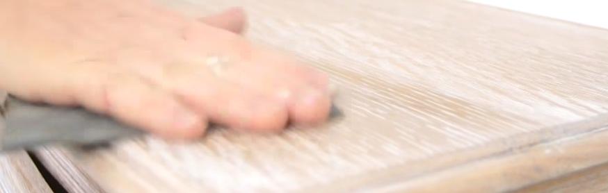 Ponçage d'un meuble en bois après l'application d'une pâte à céruser